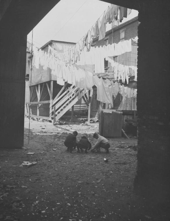 Photographie en noir et blanc montrant une cour avec des vêtements suspendus à des cordes à linge. Trois enfants jouent sur le sol.