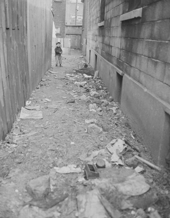Photographie en noir et blanc montrant une ruelle longue et étroite jonchée de déchets. Un jeune enfant se tient à l'autre extrémité de la ruelle et regarde le photographe.