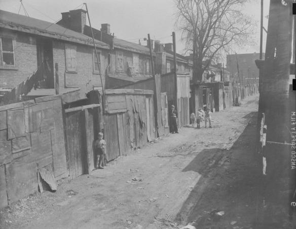 Photographie en noir et blanc montrant une ruelle délabrée derrière une rangée de maisons. Des enfants regardent vers le photographe.