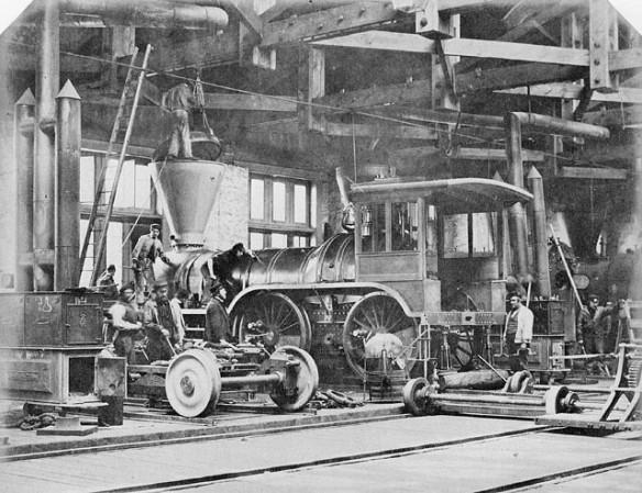 Photographie en noir et blanc montrant une locomotive en cours de construction.