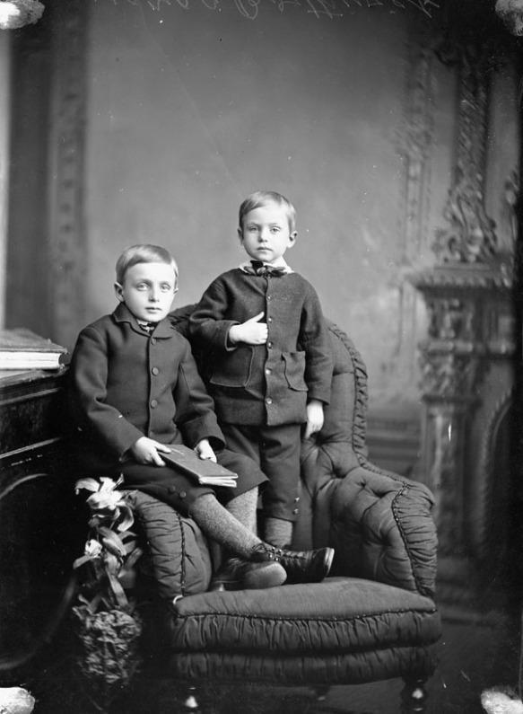 Photographie en noir et blanc de deux jeunes garçons portant des vestes noires, l'un est assis sur l'accoudoir d'une chaise et l'autre est debout sur la même chaise.