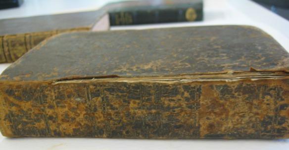 Photographie en couleur montrant plusieurs livres sur une table. Le livre à l'avant-plan présente un cuir extrêmement détérioré, et le dos du livre s'est détaché de la couverture.