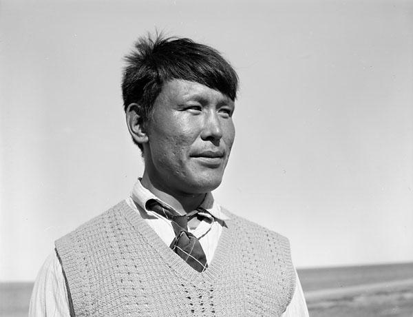 Photographie noir et blanc prise de près d'un homme Inuit portant un veston et une cravate debout à l'extérieur.