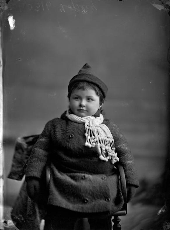 Photographie en noir et blanc d'une petite fille dans des vêtements d'hiver.