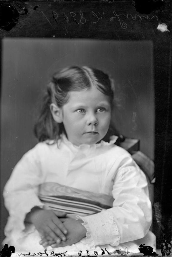Photographie en noir et blanc d'une petite fille dans une robe blanche.