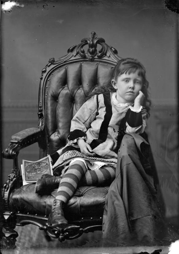 Photographie en noir et blanc d'une petite fille, le menton appuyé sur la main, un livre à côté d'elle.