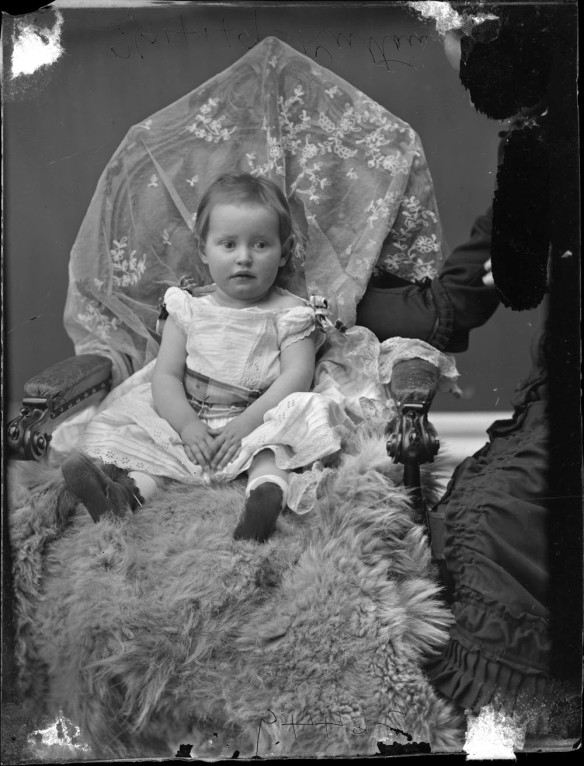 Photographie en noir et blanc d'un jeune enfant avec sa mère à droite, partiellement cachée.