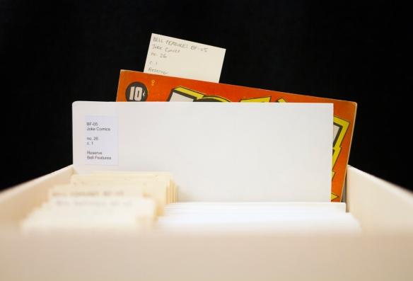 Photographie en couleur montrant une boîte contenant des fichiers avec des étiquettes. Un fichier est à moitié sortie de la boîte et montre une BD avec une couverture rouge avec le prix modique de 10¢.