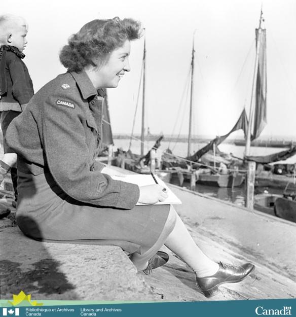 Photographie en noir et blanc prise de côté montrant une femme en uniforme souriante assise sur un quai avec un tableau à dessin et un crayon dans la main. En arrière-plan, on voit un jeune enfant blond et des voiliers à quai.