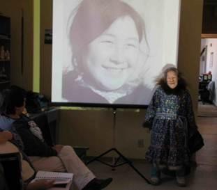 Photographie en couleur prise dans une salle communautaire à Kugluktuk, au Nunavut, en février 2011. On y voit une femme âgée inuite, vêtue d'un long parka à motif floral bordé de fourrure; elle se tient devant une toile où est projetée une diapositive d'elle-même quand elle était jeune femme.