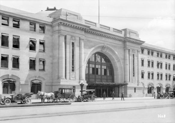 Une photographie en noir et blanc illustrant l'entrée d'un imposant édifice. Des automobiles et des carrioles tirées par des chevaux attendent en file, et des gens sont debout près de l'entrée.