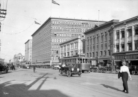 Une photographie en noir et blanc d'une large rue achalandée; on y voit des tramways, des automobiles, des carrioles tirées par des chevaux, des cyclistes et des piétons. Les édifices bordant la rue semblent récents et dénotent une certaine prospérité.