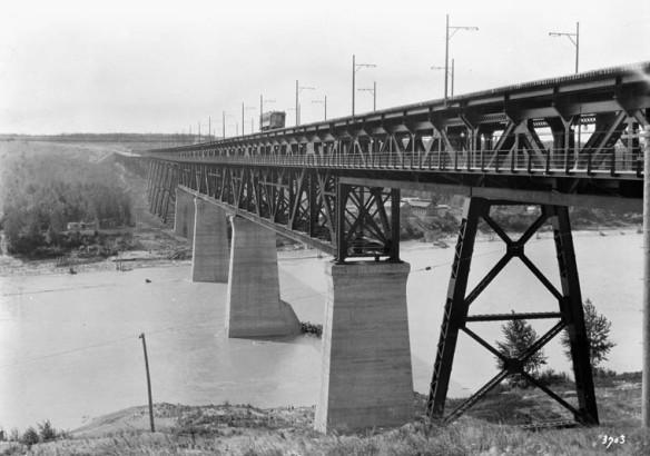 Une photographie en noir et blanc d'un pont ferroviaire en contre-haut surplombant une rivière.