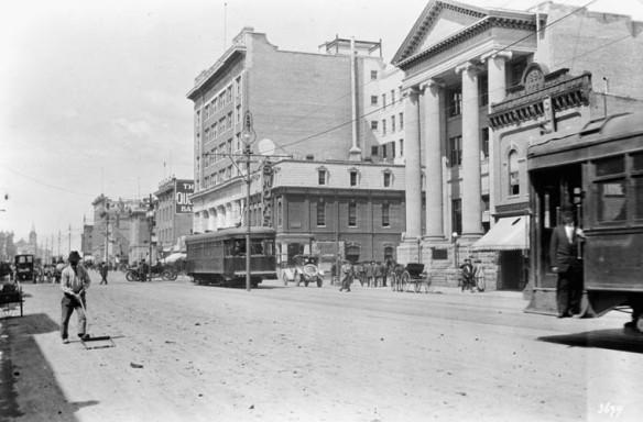 Une photographie en noir et blanc d'une large avenue, grossièrement pavée, où des tramways, des carrioles tirées par des chevaux et des automobiles se côtoient. Il s'agit de l'image d'une rue bourdonnant d'activité.