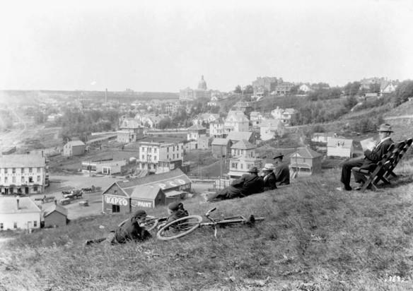 Une photographie en noir et blanc prise à partir d'une colline surplombant une ville; on y voit des cyclistes qui se reposent couchés dans l'herbe et, à proximité, d'autres hommes sont assis.