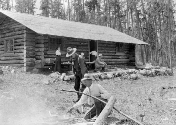 Une photo en noir et blanc, montrant un groupe de personnes devant une cabane rustique en bois rond.