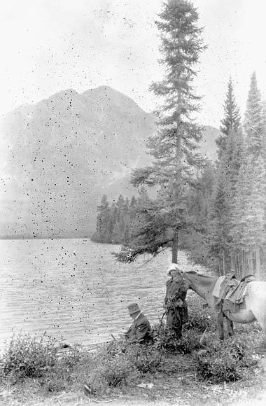 Une photographie en noir et blanc montrant un homme et une femme avec un cheval près d'un lac. L'homme est assis et la femme tient la bride du cheval. Il y a de grands conifères derrière eux.