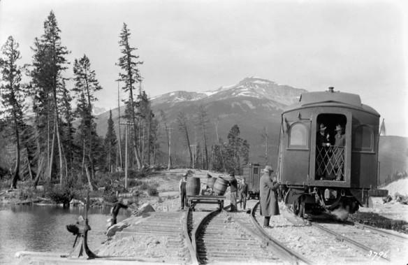 Une photographie en noir et blanc montrant un train arrêté près d'une rivière.