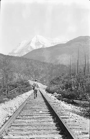 Une photographie en noir et blanc montrant un homme marchant sur la voie ferrée, en direction du mont Robson, qu'on distingue au loin.