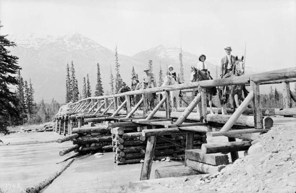 Une photo en noir et blanc montrant une personne à pied et cinq autres à cheval, traversant un cours d'eau sur un pont en bois rond; il y a des montagnes en arrière-plan.