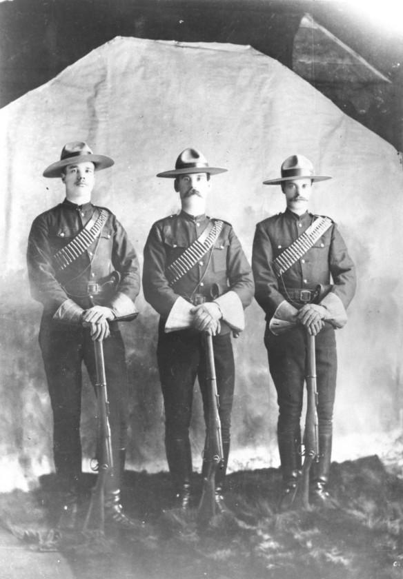 Trois officiers de la Police à cheval du Nord-Ouest au repos, en uniforme, les mains croisées sur l'extrémité de leurs fusils.