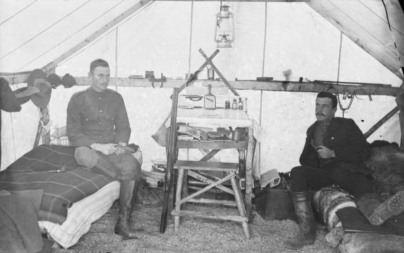 Photo en noir et blanc de deux hommes en uniforme de la Police à cheval du Nord-Ouest, assis sur des lits de camp dans une tente.