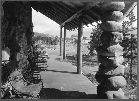 Une photographie en noir et blanc montrant une galerie avec des sièges pour profiter du panorama. Le style architectural est rustique, avec des pierres de rivière et des billots en bois rond sommairement dégrossis.