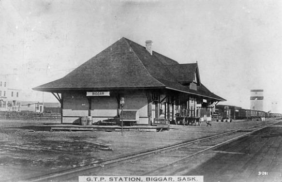 Une photographie en noir et blanc d'une gare de train, prise de l'autre côté de la voie ferrée. On y voit une affiche arborant le mot « Biggar », et une note au bas de la photographie qui indique qu'il s'agit de la gare G.T.P., à Biggar (Saskatchewan).