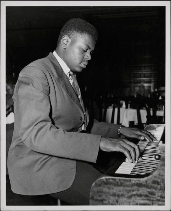 Une photographie en noir et blanc montrant Oscar Peterson jouant du piano dans un cabaret.