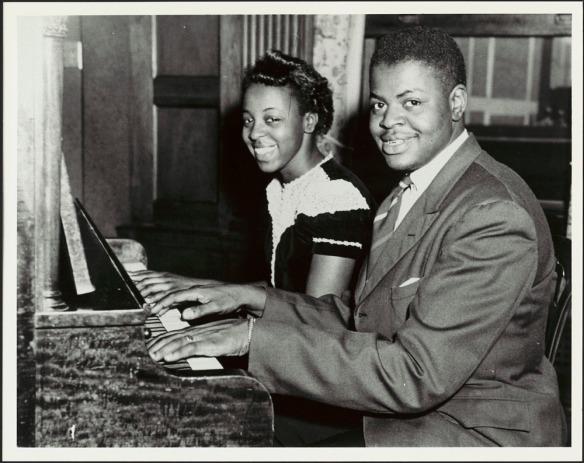 Une photographie en noir et blanc d'Oscar Peterson et de sa sœur Daisy, assis au piano avec leurs mains sur le clavier. Ils regardent vers le photographe et sourient.
