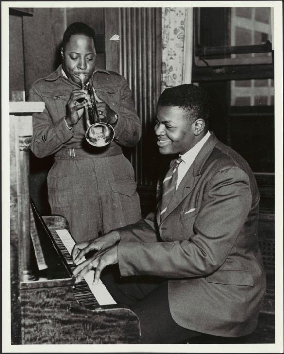 Une photographie en noir et blanc montrant Oscar Peterson assis, jouant du piano. Son frère Charles, vêtu de l'uniforme de l'Armée canadienne, est debout à côté de lui et joue de la trompette.