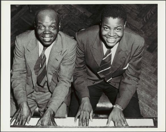 Une photographie en noir et blanc montrant Oscar Peterson avec son père Daniel. Les deux hommes sont assis au piano, leurs mains sur le clavier, souriant et regardant le photographe vers le haut.