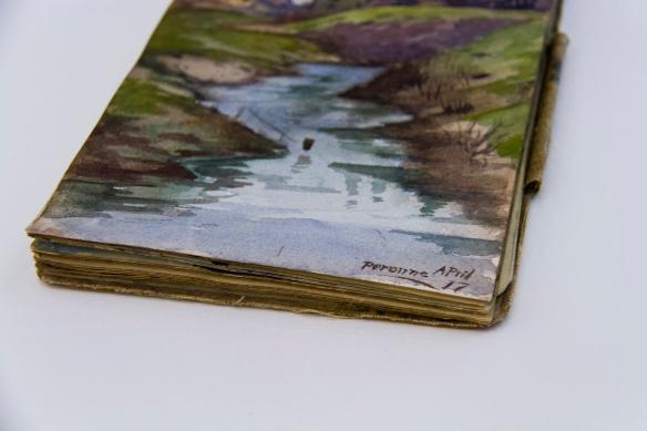 Une photographie couleur d'un cahier de dessins vu de biais, montrant les berges d'une rivière avec la date et le lieu dans le coin inférieur droit, « Perrone avril 17 ».