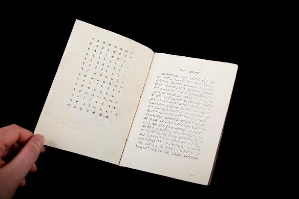 Image en couleur d'un livre écrit en caractères syllabiques inuktitut. Le livre est ouvert pour montrer les deux premières pages. Celle de gauche présente le syllabaire inuktitut et celle de droite présente un texte rédigé en syllabique inuktitut.