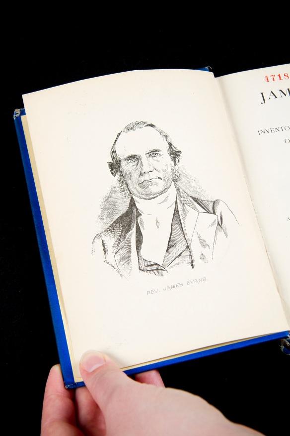 Une photo en couleur montre une main tenant un livre par le coin inférieur gauche. Le livre est ouvert à la page frontispice, où l'on voit un portrait dessiné du missionnaire méthodiste James Evans; celui-ci porte des vêtements typiques du 19e siècle et regarde directement le lecteur.
