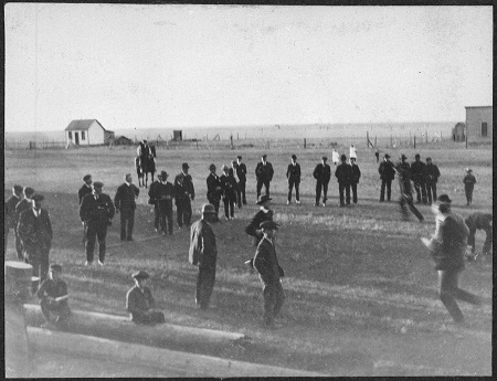 Une photographie en noir et blanc d'un groupe d'hommes debout dans un champ regardant un match de duck on a rock.