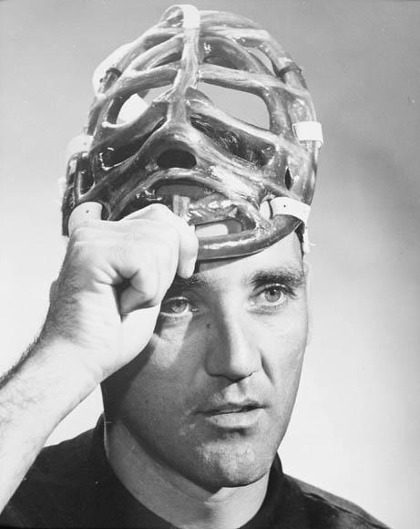 Photographie en noir et blanc d'un homme qui enlève son masque de gardien de but.
