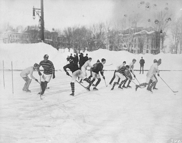 Une photo noir et blanc montrant des joueurs de hockey lors d'une partie sur une patinoire extérieure