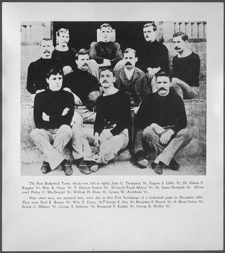 Photographie en noir et blanc montrant un groupe d'hommes assis dans un escalier. De chaque côté, il y a les paniers qui étaient utilisés à l'époque dans ce sport.