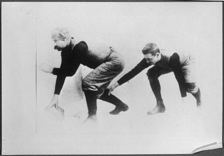 Une photographie en noir et blanc de deux joueurs de football rugby accroupis, l'homme sur la gauche tient le ballon et attend de le lancer à l'autre homme derrière lui.