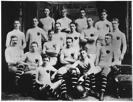 Une photographie en noir et blanc de l'équipe de football rugby de l'Université McGill. Les joueurs portent des chaussettes montantes rayées et un uniforme blanc orné d'un écusson.