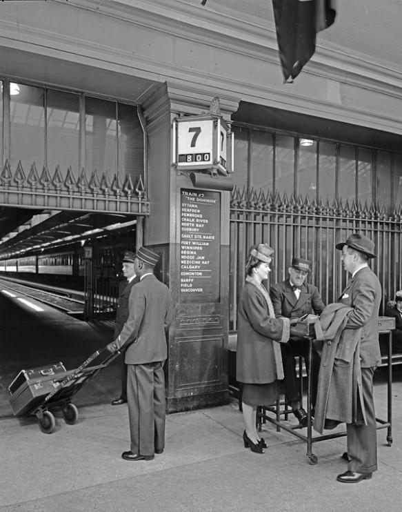 Photographie en noir et blanc de personnes à une gare. Un porteur transportant des bagages sur un chariot est vu de dos. Deux passagers élégamment vêtus discutent avec un préposé aux billets. Sur le mur derrière eux, un panneau d'information annonce le train Dominion, qui part de Montréal pour se rendre à Vancouver. Un train de voyageurs est visible à l'arrière-plan.