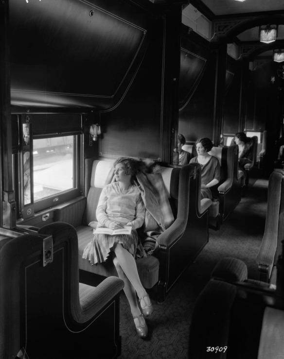 Photographie en noir et blanc de passagères assises dans une voiture-lits, regardant par les fenêtres.