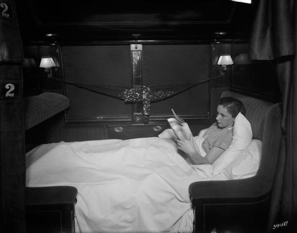 Photographie en noir et blanc d'une femme de profil, étendue sous les couvertures de la couchette inférieure, lisant un journal.