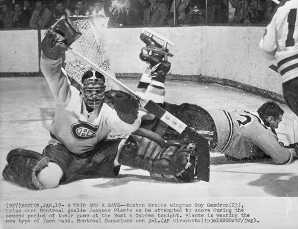 Photographie en noir et blanc d'un gardien de but masqué défendant son but. Derrière lui, d'autres joueurs (sans casque) qui tombent sur la glace, tentant de s'emparer de la rondelle.