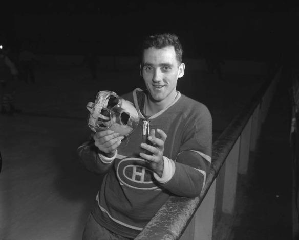 Photographie en noir et blanc d'un homme appuyé contre les bandes d'une patinoire et tenant un masque transparent dans les mains.