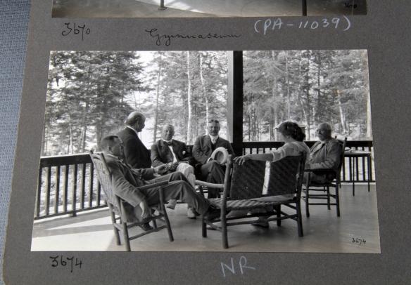 Photographie en noir et blanc d'un groupe de personnes assis sur une véranda qui donne sur un boisé.