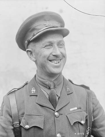 Photographie en noir et blanc montrant un homme tout sourire dans un uniforme d'officier avec une casquette.