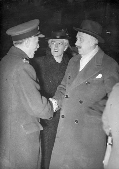 Photographie en noir et blanc de deux hommes et une femme. Les hommes se serrent la main, et la femme regarde l'un des hommes.