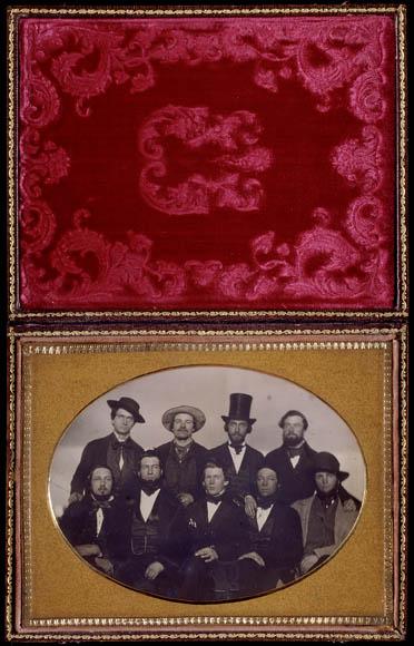 Un cadre de daguerréotype bordé de velours contenant le portrait de neuf hommes; cinq assis à l'avant, quatre debout à l'arrière.